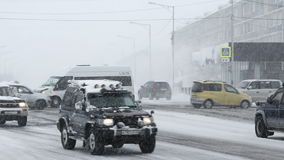 Snow covered cars driving on road in city during heavy snowstorm blizzard. PETROPAVLOVSK-KAMCHATSKY CITY, KAMCHATKA PENINSULA, RUSSIA - JANUARY 12, 2017: Winter stock video