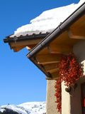 Snow covered chalet in winter. Closeup of snow covered chalet in winter with Alps mountains in background, Austria Stock Images