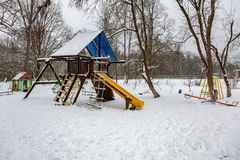 Children`s playground in winter. Snow-covered children`s playground with swing and slide in public park in winter Royalty Free Stock Photo