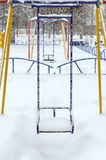 Snow-covered children`s swings. Winter landscape Royalty Free Stock Image