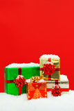 Snow covered Christmas presents red background. Stock Photo