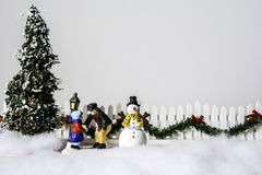 Christmas Tree and Snow Man. A snow covered Christmas scene with father and daughter between decorated tree and snow man white picket fence with garland and Royalty Free Stock Images