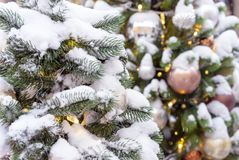 Snow-covered Christmas tree with toys and a garland royalty free stock photography