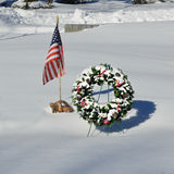 Snow Covered Christmas Wreath with American Flag. A snow covered Christmas evergreen wreath with pinecones and berries by an American Flag and World War Two royalty free stock photo