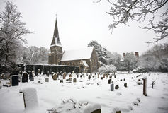 Snow covered church and grave yard Royalty Free Stock Photography
