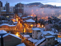 Snow-covered city. A picture of a crowded city, covered in snow and lighted by the orange street lights Stock Photo