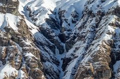 Snow Covered Cliff Face Background. A beautiful Rocky Snow Covered Cliff Face background royalty free stock photography
