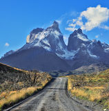Snow-covered cliffs of Los Cuernos. Dreamland Patagonia. Snow-covered cliffs of Los Cuernos, to them is a road of black gravel stock photography