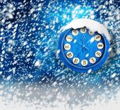 Snow-covered clock on abstract background Royalty Free Stock Photo