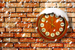 Snow-covered clock on background of brick wall Royalty Free Stock Image