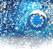 Snow-covered clock on blue background Stock Photo