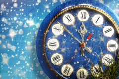 Snow-covered clock on  blue background Royalty Free Stock Photo