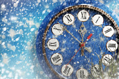 Snow-covered clock on  blue background Royalty Free Stock Image