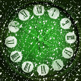 Snow-covered clock on green background Stock Images