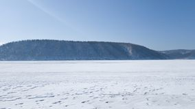 Snow-covered coast of the Angara river on a spring day. Travel to frosty Siberia.  royalty free stock photo