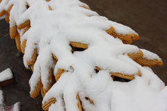 Snow covered corns hanging on the roof in the countryside.  Stock Photos