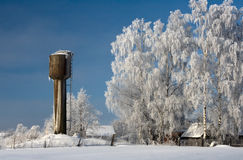 Snow covered cottage. Winter in the countryside. Small wooden house - a rural cottage and water tower Stock Photography