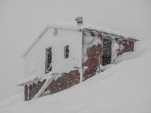 Snow-covered cottedge on the snow slope of mountain Stock Photos