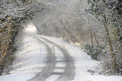 Snow covered country lane and vehicle tracks Royalty Free Stock Photo