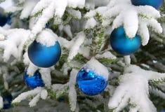 Snow-covered Dekorationkugeln, die an einem Christm hängen Stockbild