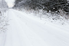 Snow-covered dirt road running Stock Photo