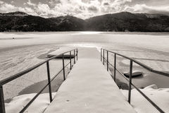 Snow covered dock by lake. Royalty Free Stock Photography