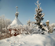 Snow covered dome with cross of orthodox chapel under hoary fir tree Stock Images