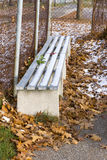 Snow covered dugout bench amidst autumn leaves during off season Stock Images