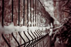 Snow-covered element of the old fence stock image