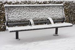 Snow covered empty bench Stock Images