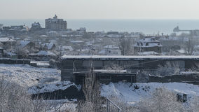 Snow-covered factory and the city on a winter morning royalty free stock photos