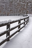 Snow covered fence. Snow covered wooden fence line that borders a field Stock Images