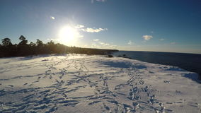 Snow covered field on a cliff next to  the ocean stock video