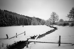 Snow covered field with creek Royalty Free Stock Photography