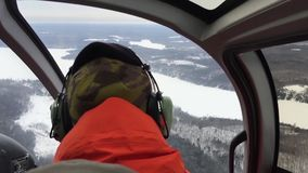 Pilot taking a sharp turn in helicopter. Snow covered field seen from helicopter- aerial view stock video