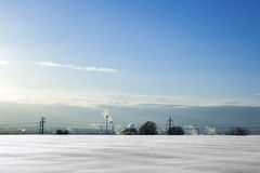 Snow covered field and smoking chimneys Stock Photo