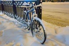 Snow-covered fiets op de omheining wordt geparkeerd die stock foto's