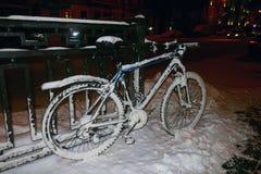 Snow-covered fiets op de omheining wordt geparkeerd die royalty-vrije stock afbeeldingen