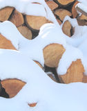 Snow Covered Firewood. Stack of cut firewood covered in a layer of white fluffy snow stock image