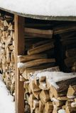 Snow-covered firewood stacked under a canopy, firewood for the winter. Winter landscape stock photography
