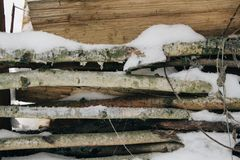 Snow-covered firewood stacked under a canopy, firewood for the winter. Winter landscape stock photo