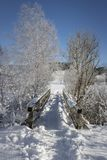 Snow covered footbridge on a sunny winter day stock photo