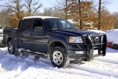 Snow Covered Ford Truck, 4 Doo. A blue 2004 Ford F150 four wheel drive truck with grill guard covered in snow and ice Royalty Free Stock Photo
