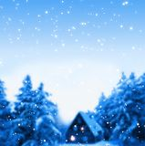 Snow-covered forest hut in winter forest blue blur background. Wooden hut under snow-covered firs. In the windows the lights burn. With the evening sky snow Royalty Free Stock Photos