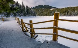 Snow covered forest lake Synevyr in Carpathians. Wooden pier on snow covered forest lake Synevyr in Carpathian mountains. gorgeous winter landscape of a popular stock photography