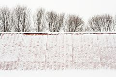 Snow covered gable roof and leafless trees. In winter stock photo