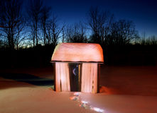 Snow covered glowing outhouse. A rural outhouse with footsteps in the snow leading up to it, with a twilight sky behind Royalty Free Stock Photos
