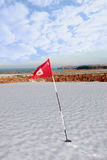 Snow covered golf course and cliffs with flag