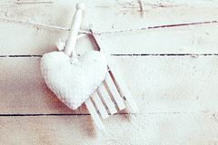 Snow covered heart pegged on a line. In front of a wooden wall with copy space in an apres ski love and romance conceot stock images
