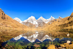 Snow covered high peaks reflected on a lake Stock Image